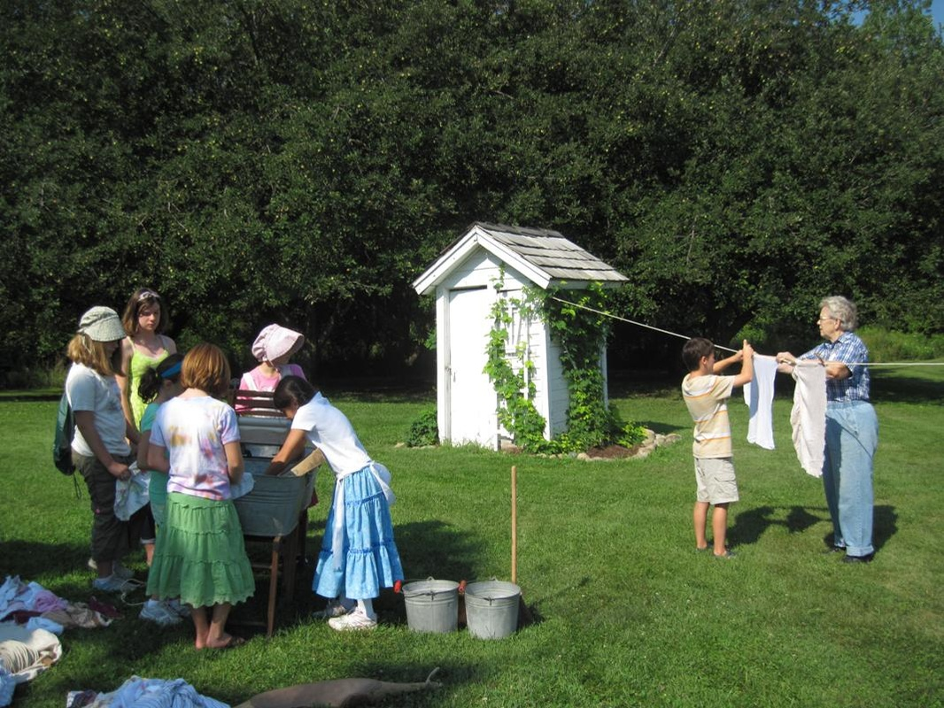 Schoolchildren learn how to wash clothes using a washtub and hand wringer