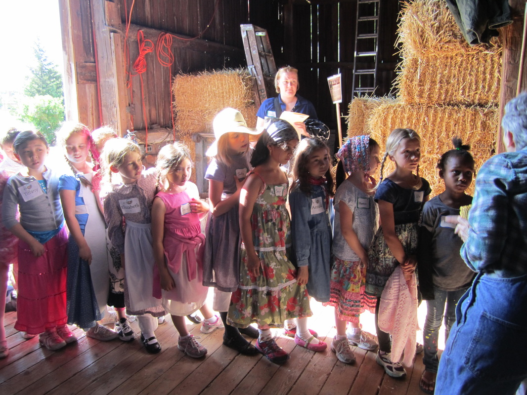 Schoolchildren listen to a program held in the barn