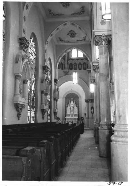 Interior view of church showing altar, elaborate ceiling and wall moldings, and pews