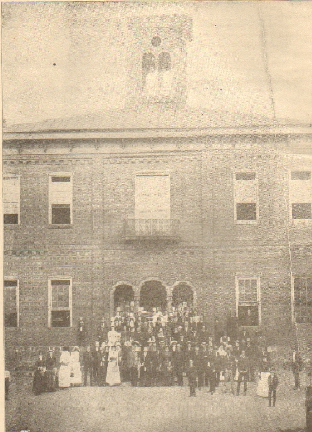 Black and white print of the third Harrison County Courthouse which existed from 1857-1887. The construction began on this building in 1855. This courthouse had a triple arch entrance with a second-floor balcony and central bell tower.