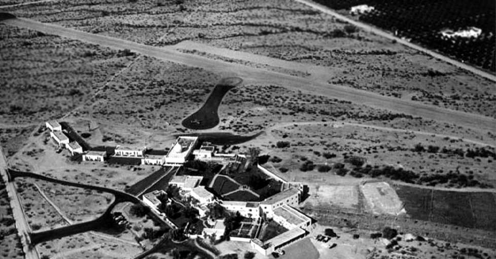 A circa 1958 aerial view looking northeast at the Casa Blanca Airfield. It shows the hotel buildings in the foreground, with a single aircraft on the asphalt taxiway leading to the runway. (Scottsdale Public Library)