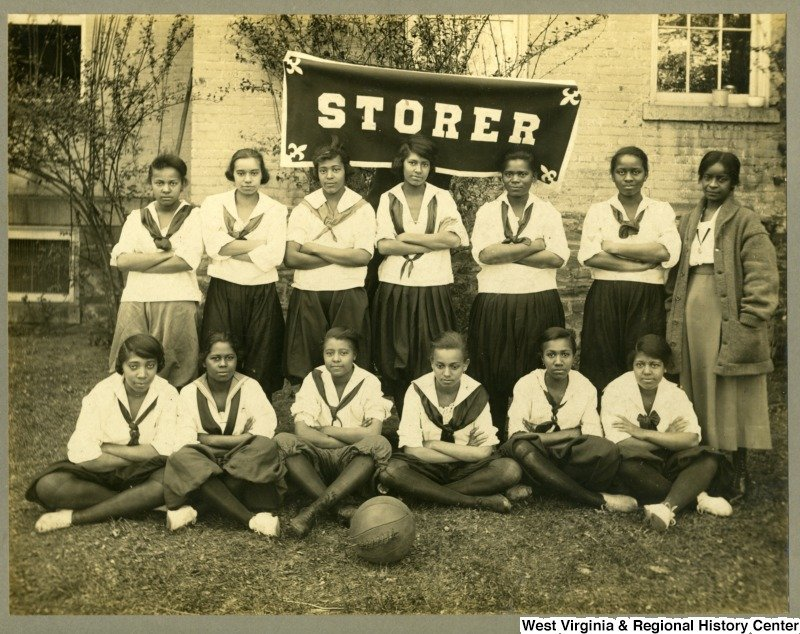 The girl's basketball team pose in their uniforms. Photo circa 1920, courtesy of West Virginia and Regional History Center, WVU Libraries.