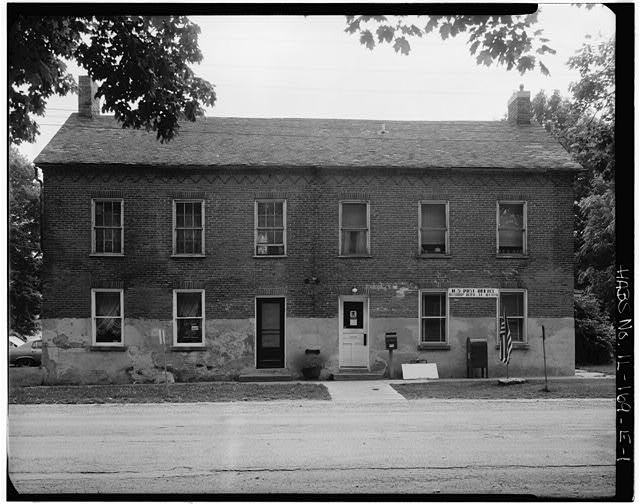 This undated photo from the Library of Congress shows the carpenter shop before the recent renovation. Note the variation in windows and the stucco that was added post colony period but removed during renovations.