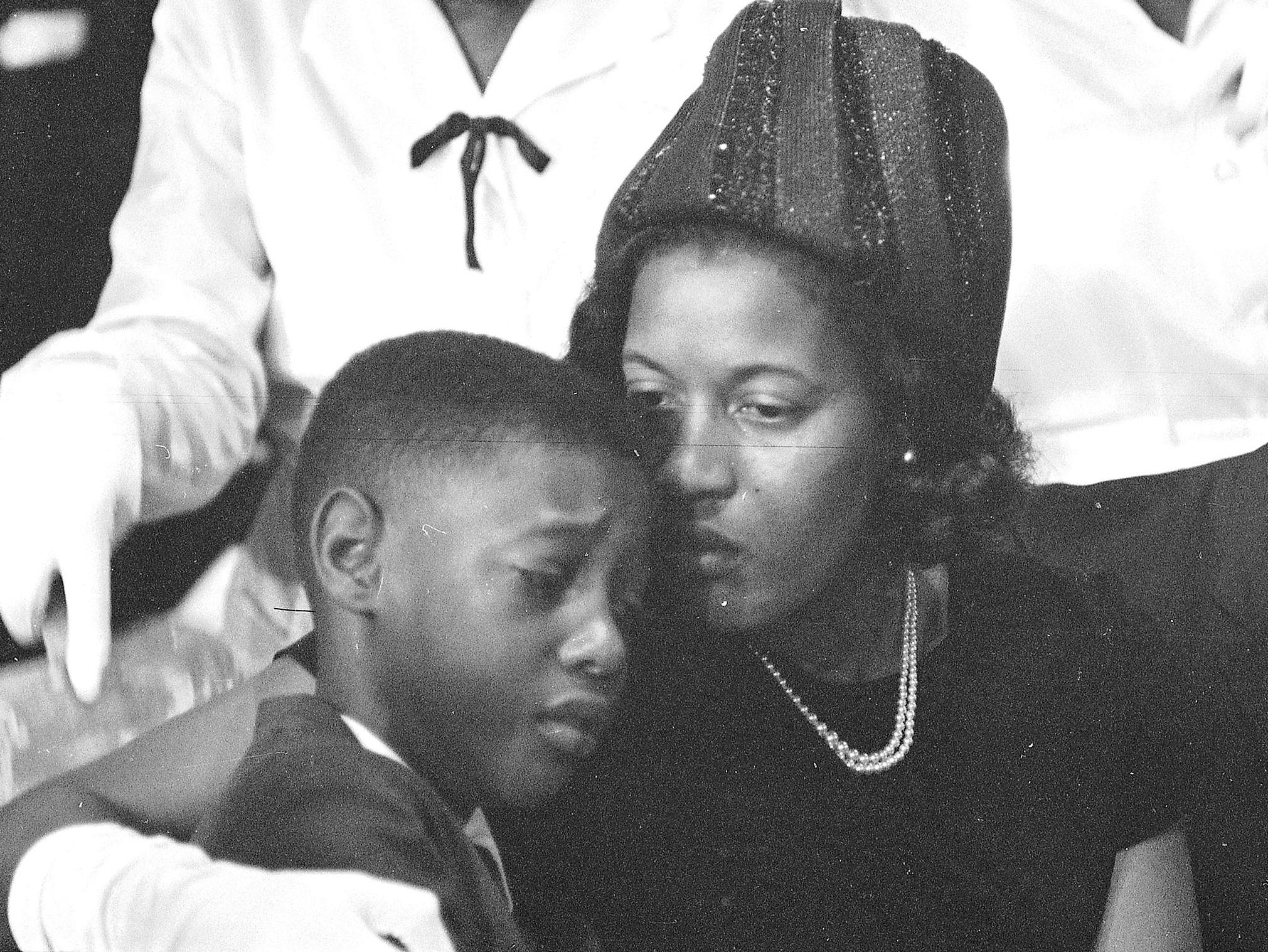 Myrlie consoles her son at the funeral of his father.
