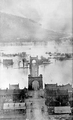 Oldest known photo of the Wheeling Suspension Bridge. Notice the flooded Ohio River, photographed 1852. Notice flooded Wheeling Island at the end of the bridge. W.C. Brown Collection.