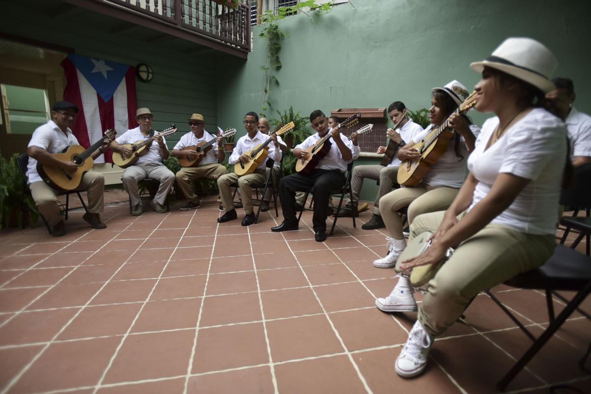 A group of musicians playing instruments like: cuatro, guitars, and traditional drums