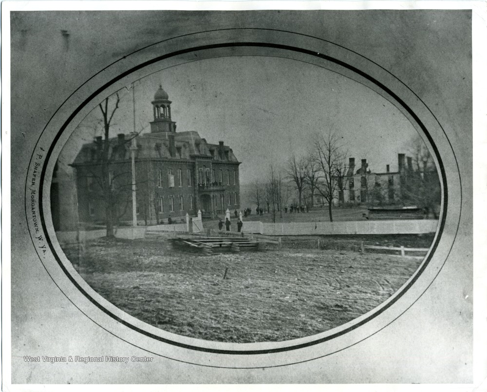 The burnt out foundation of the Woodburn Female Seminary following an 1873 fire. Martin Hall, WVU's oldest building appears on the left. Woodburn Hall was erected on the site of the seminary.