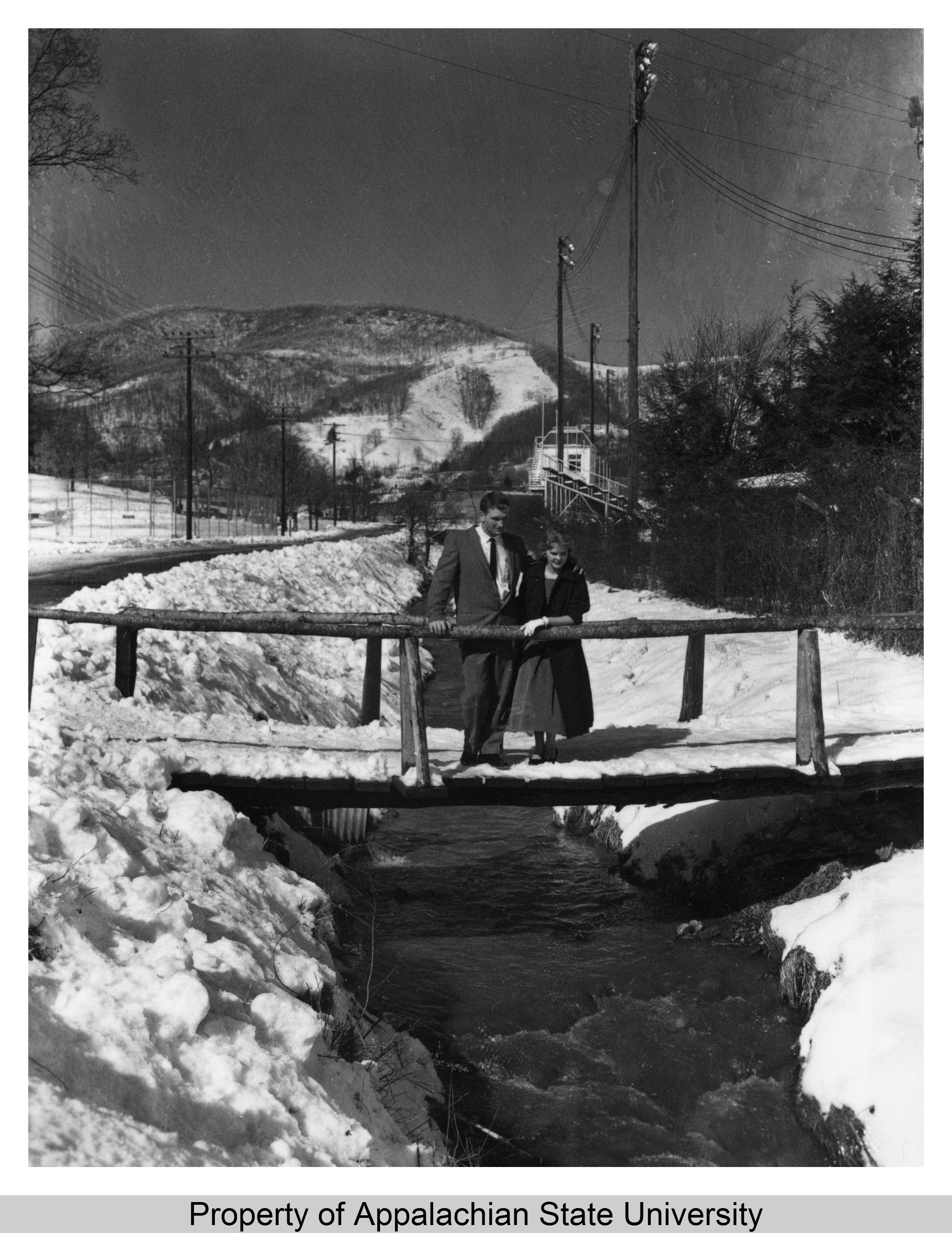 Two students stand on a snowy bridge over Kraut Creek in 1957.