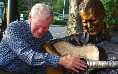 This 2011 photo shows Doc Watson as he is overcome by emotion as he feels the sculpture for the first time.