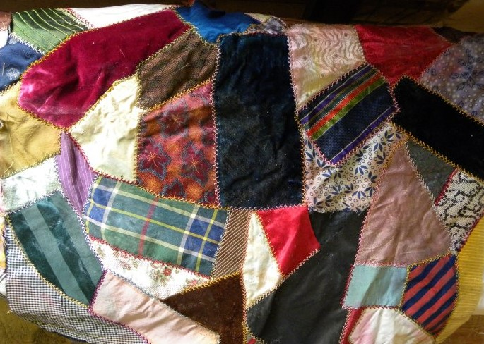A 1930s example of a crazy quilt. Notice the elaborate, visible stitching and array of colors. While this crazy quilt is small, other examples could cover an entire bed.