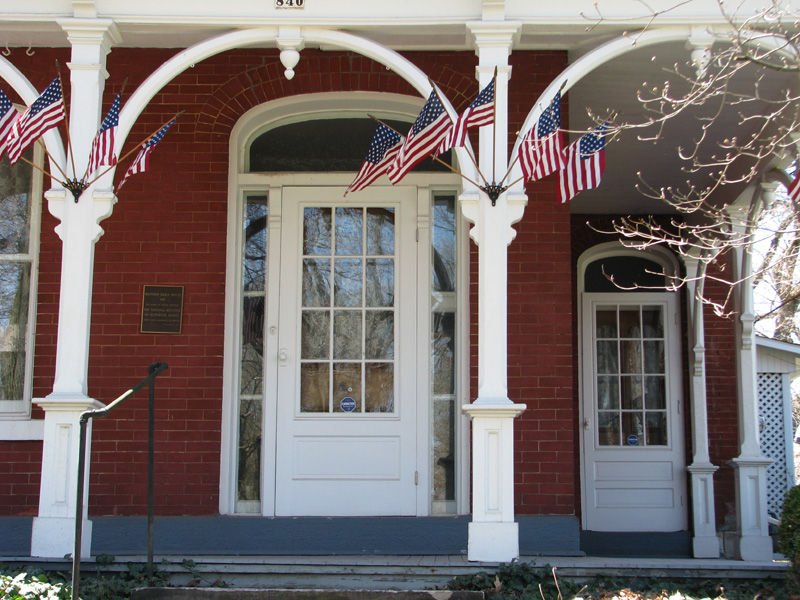 Flags decorate the wrap-around porch of the Mabel Hartzell Historical Home on days when the home is open for visitors