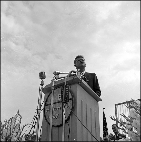 Kennedy stands at a podium at East Carolina College in front of approximately 12,000 people.