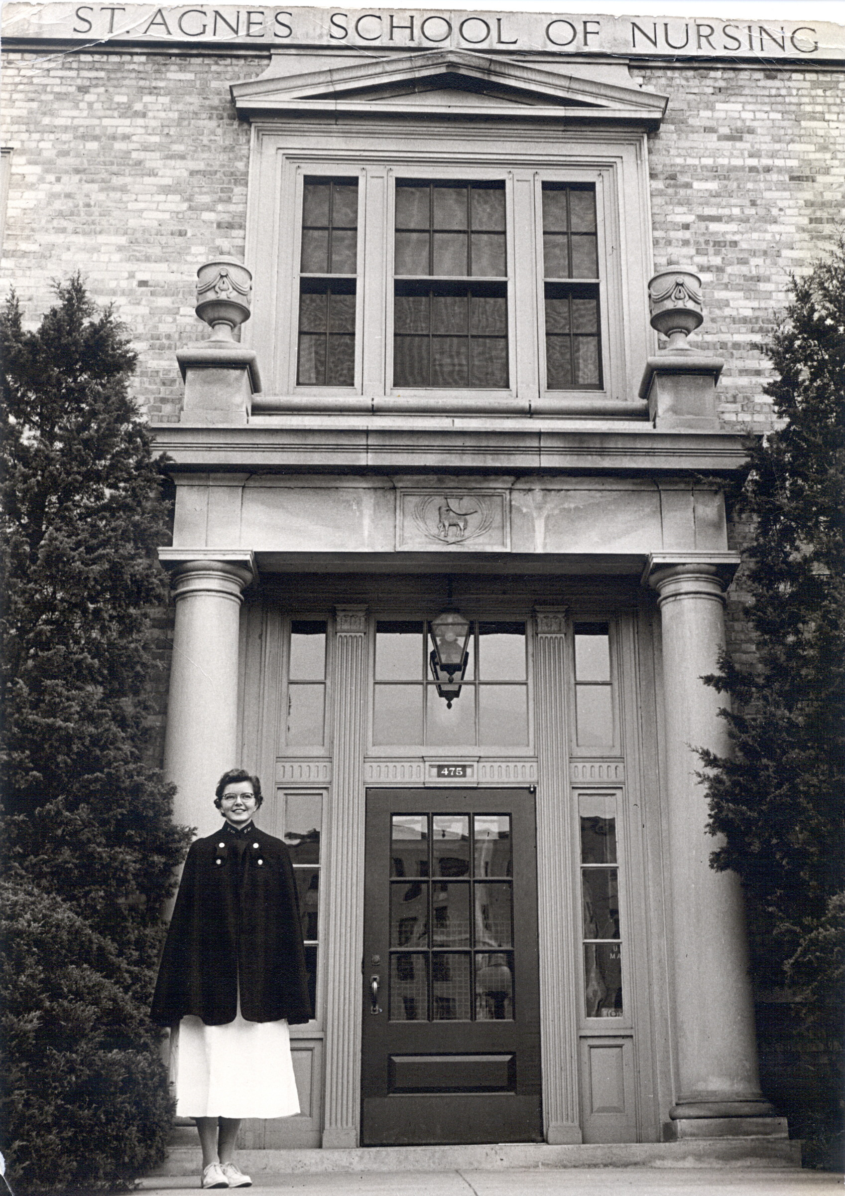 A nursing student stands outside St. Agnes School of Nursing, 1950s.