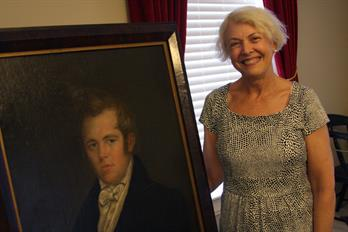 Carolyn Lansden Whittle with the portrait that she had donated with her great-great-great grandfather, David A. Smith.