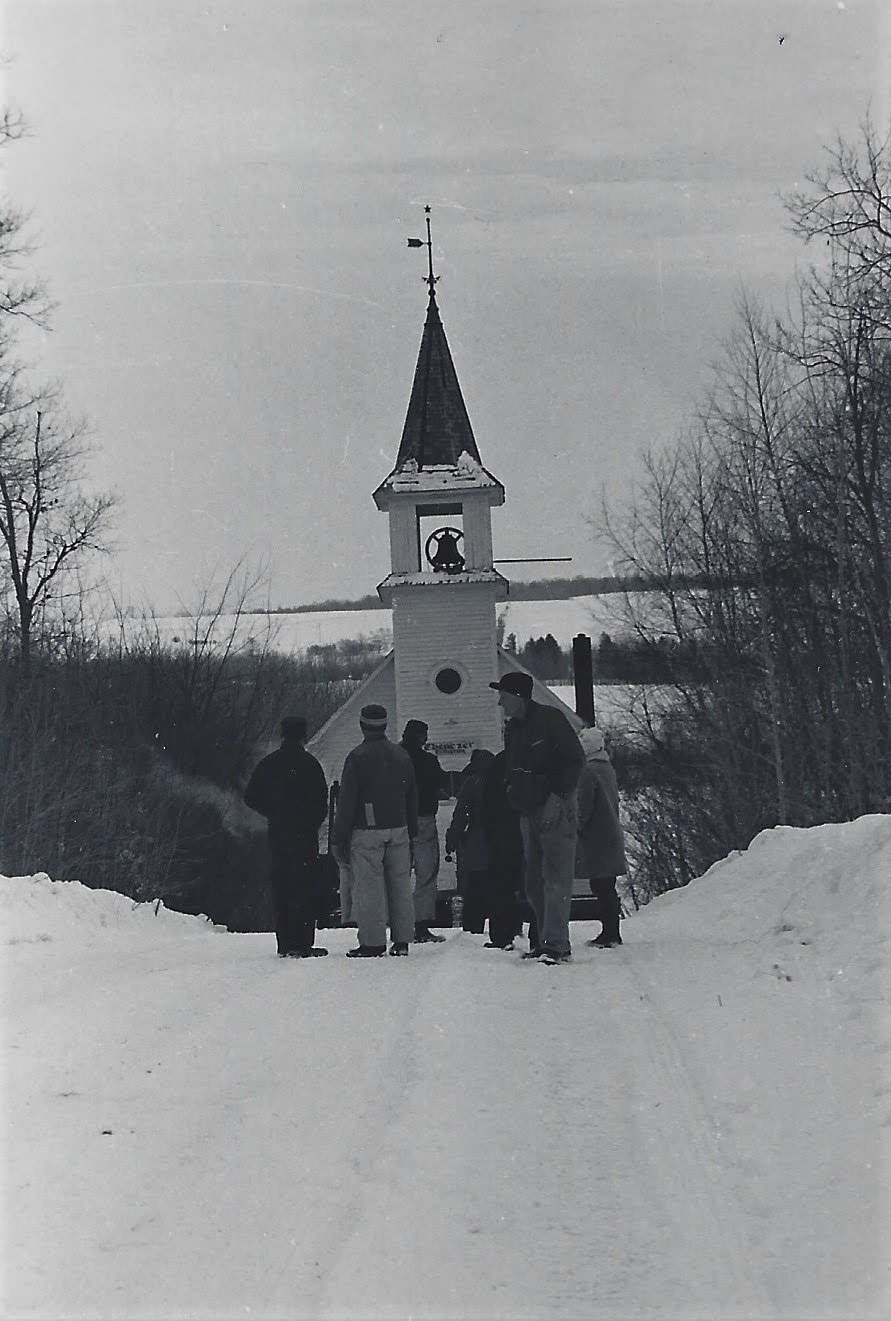 Men in winter clothing observing as the church is moved along a steep hill on a snowy road.