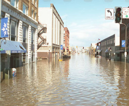 1997 photo of the intersection of 4th St and DeMers during the 1997 flood. The bank building can just been seen on the left background area. Courtesy of State Historical Society of North Dakota