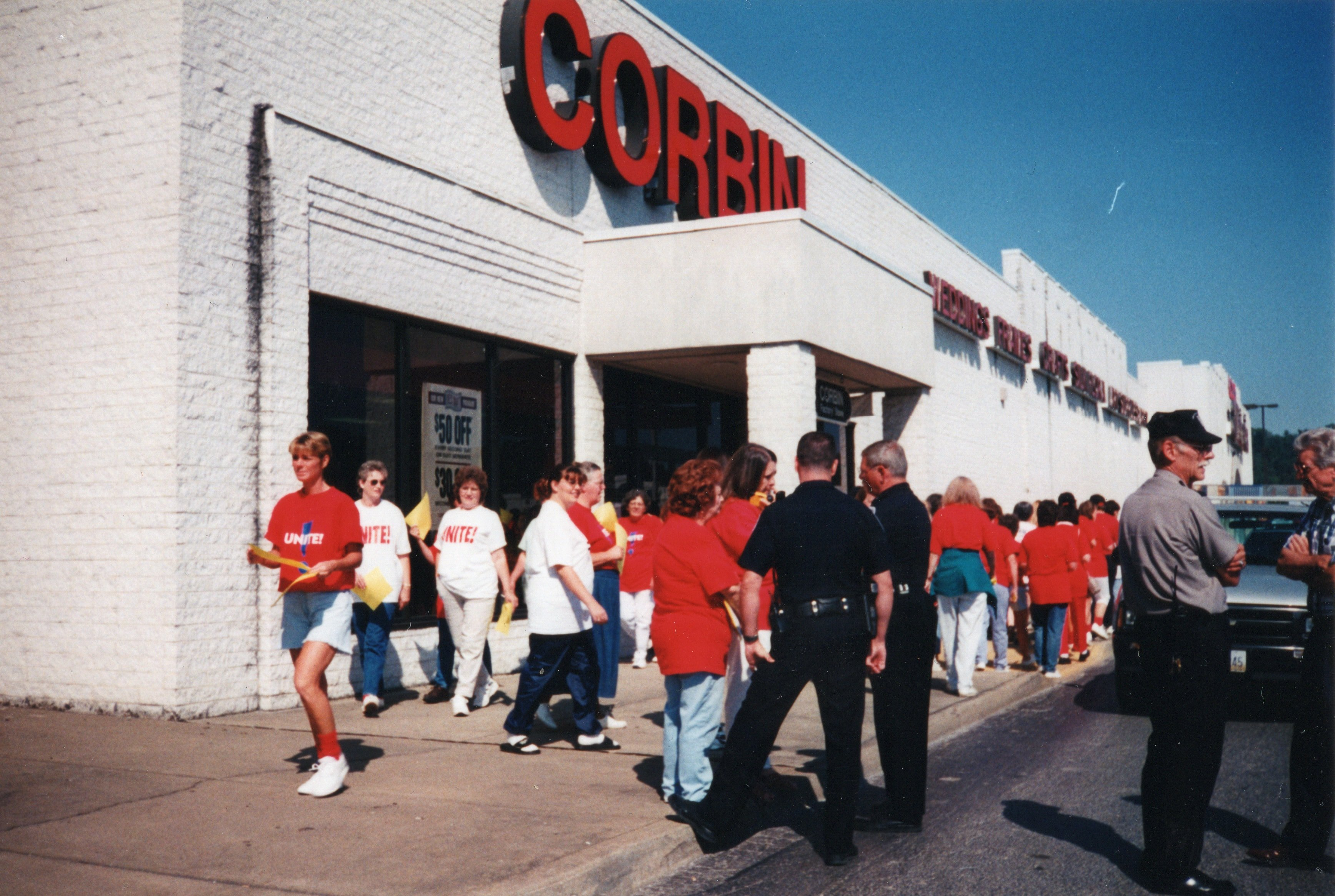 UNITE Union Protesters being questioned by police about activity and possession of necessary permits at Corbin Ltd. Factory Store at Huntington Mall, Barboursville, WV, 1996