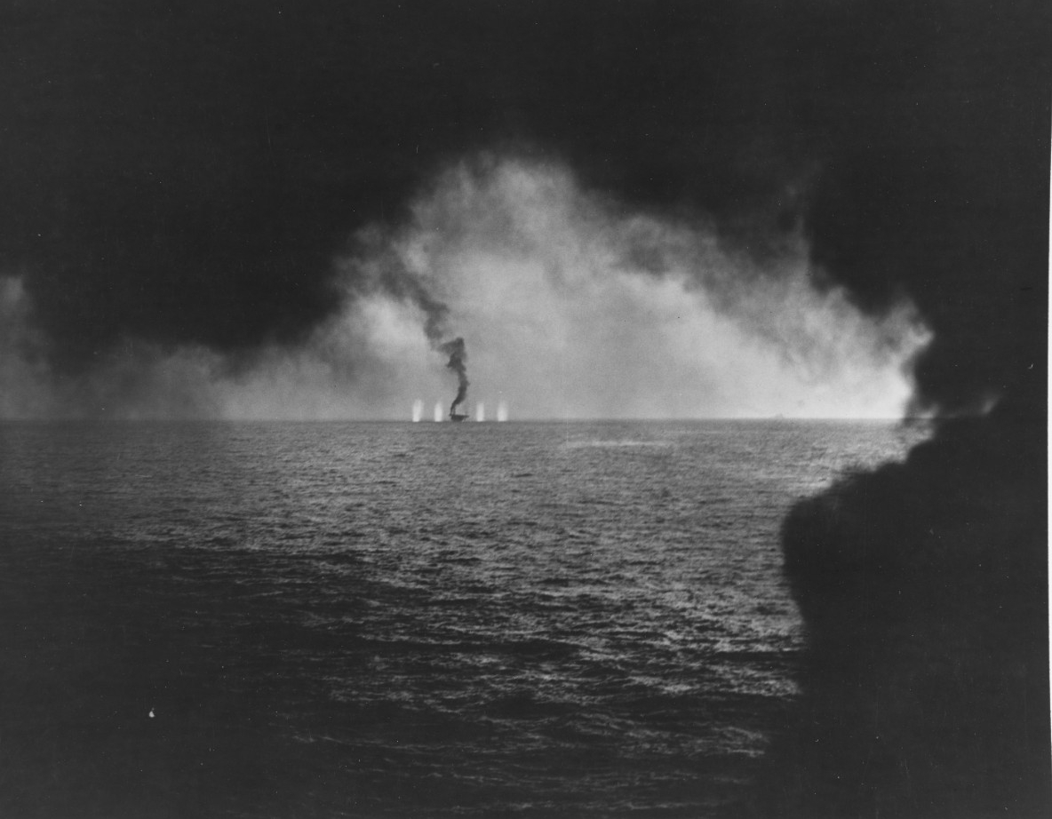 USS Gambier Bay is hit as she fall's behind her fleet, a Japanese Cruiser is barely visible in the background