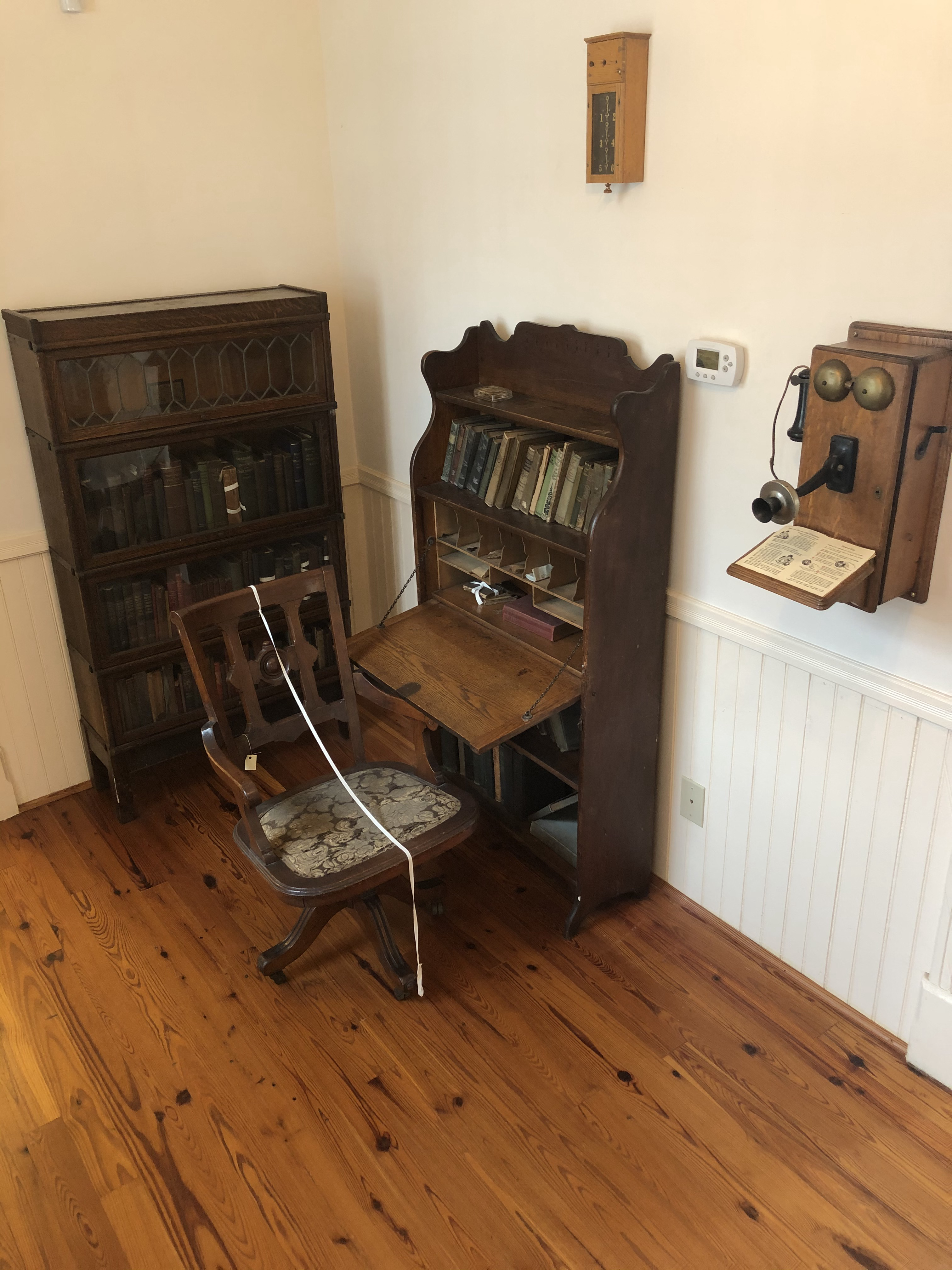 This is Dr. Pope's home patient examination area. Moving from left to right there is a bookcase that contains Dr. Pope's original medical books (pre-penicillin). Dr. Pope's original desk and chair, hanging above it is a maid's call box, and to the right is a replica of the model of phone the family would've had.