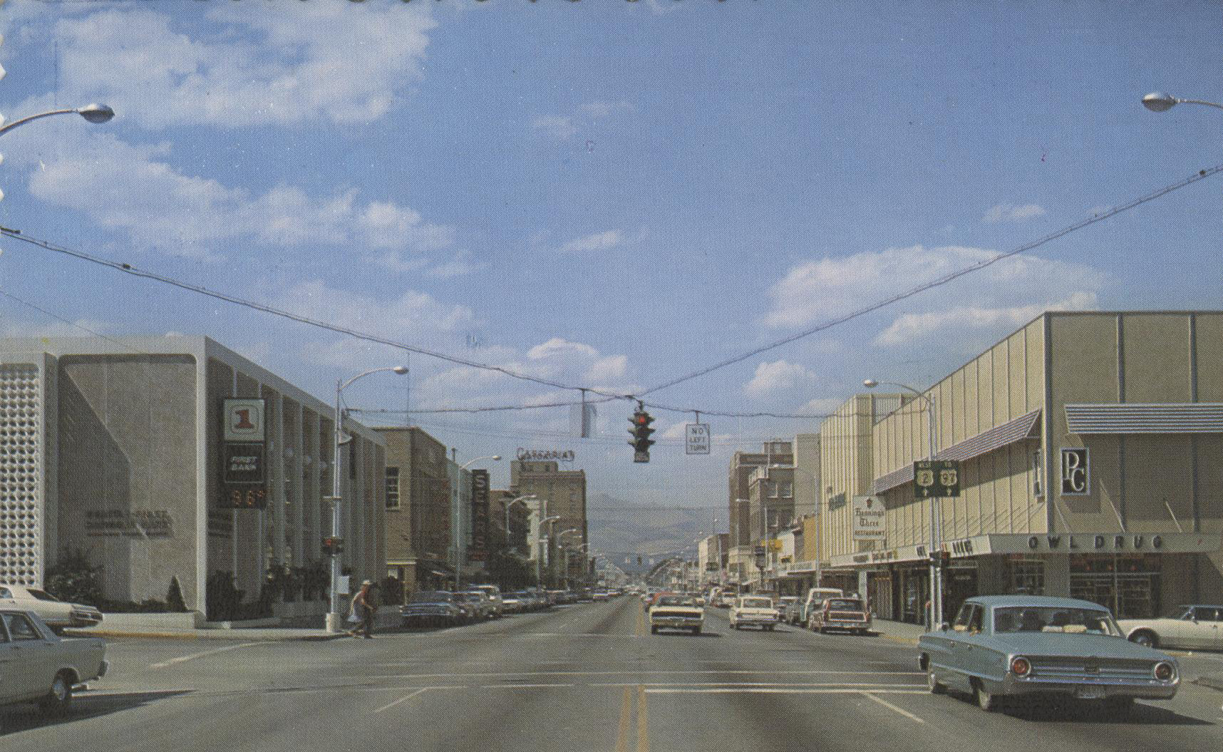 A 1965 postcard showing the view northward up Wenatchee Avenue from the intersection with Orondo Avenue.  First National Bank building on left corner, Owl Drug and the Plough Building on the right.