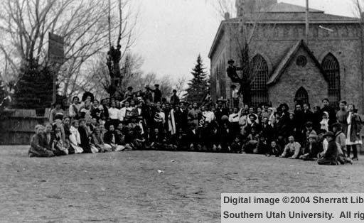 Photography courtesy of Southern Utah University Digital Library.  This image, depicting a group of people posing in front of the Cedar City Tabernacle, serves to indicate the importance and degree of use of the Tabernacle by the community.