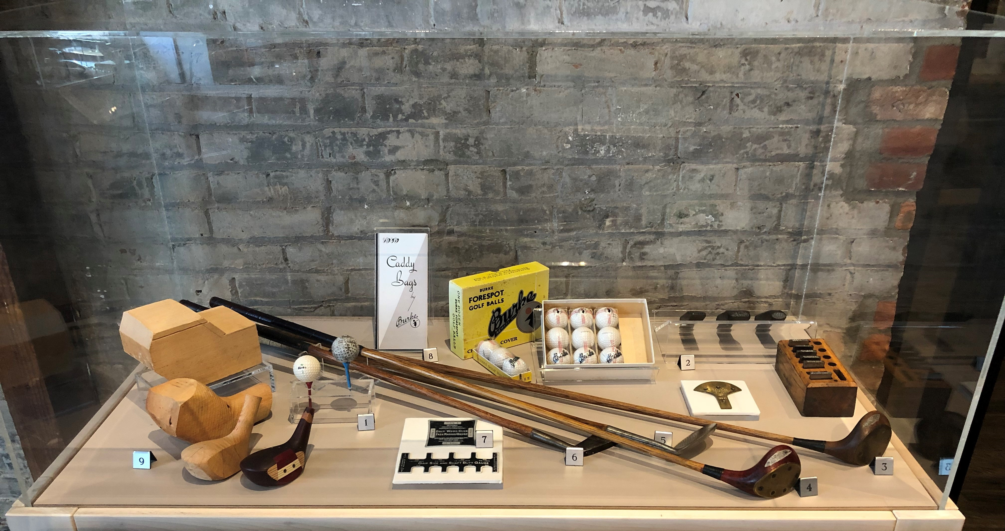 A variety of objects from the Burke Golf Company, including clubs, balls, stamps, and golf club gauges to ensure proper size.