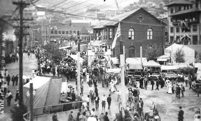 1909 photo of Bisbee during the Fourth of July festivities. The The Phelps Dodge Headquarters Building is seen in the center of the photo (side of building featured)