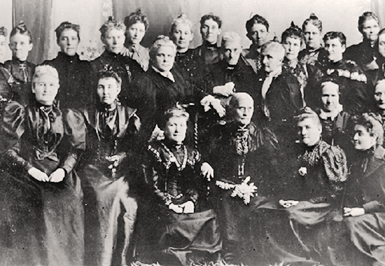 Susan B. Anthony, seated in center, wearing spectacles, and Anna Howard Shaw, standing at the left with her hand on a chair, met with a group of Utah woman suffrage leaders in 1895 after they united both of their organizations..