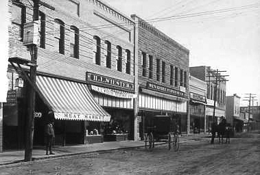 Downtown Wenatchee.  West side of North Wenatchee Avenue between Palouse Street and First Street angled looking southeasterly.  Carriage and horse rider on dirt avenue. Buildings and business from left to right include: Wiester Building with the Little-Wetsel Meat Market and Wiester Department Store; Mooney Building with the Wenatchee Furniture Company; the Scheble Hardware Company; Wenatchee Bazaar and other buildings and businesses further down.