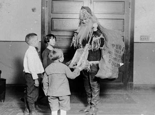 An NENH employee dressed as Santa with gifts for the children