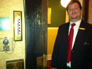 A hotel employee stands next to the hotel's fully operational 1908 Otis elevator.