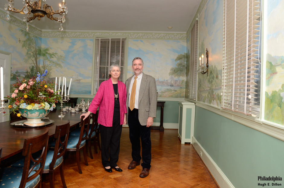 a couple stands in the mansion's Banquet Room that features a large, Dot Bunn mural depicting Philadelphia in the 19th century.