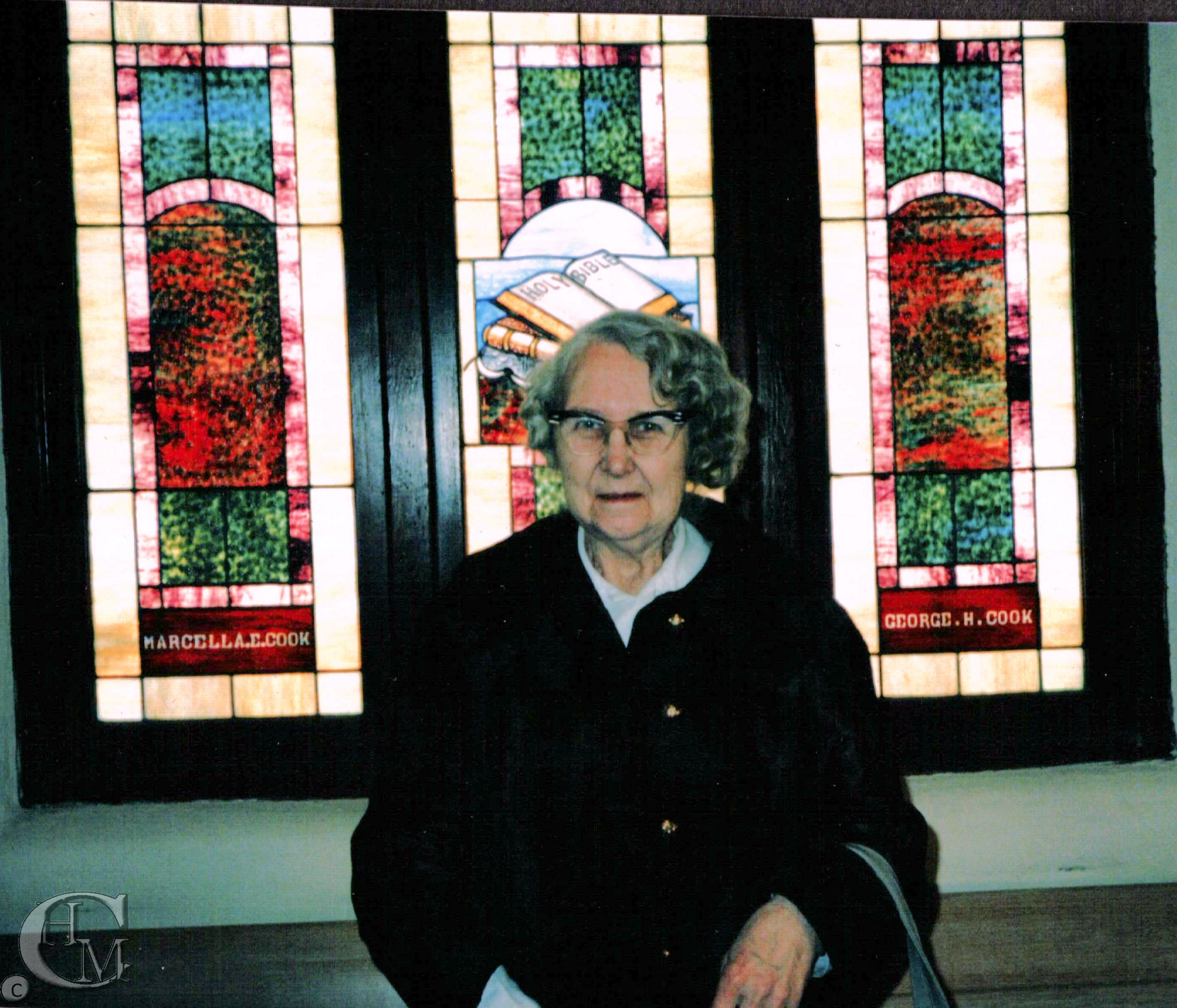 Church member, Jean Christianson stands in front of the stained glass window donated by Marcella and George Cook