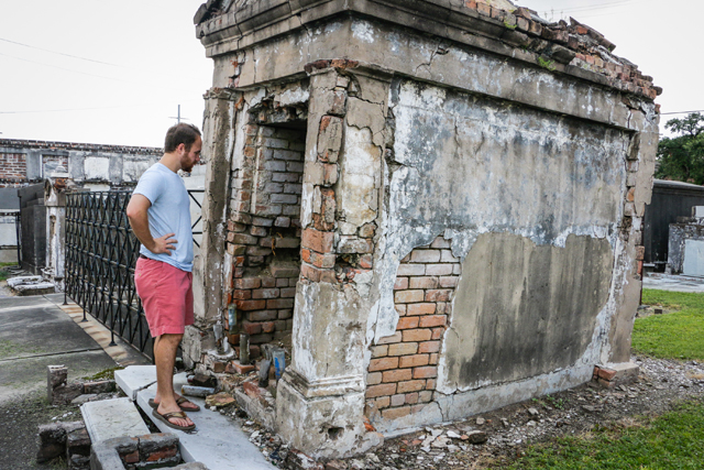 A curious visitor peers into a tomb that has been damaged by vandals and neglect.