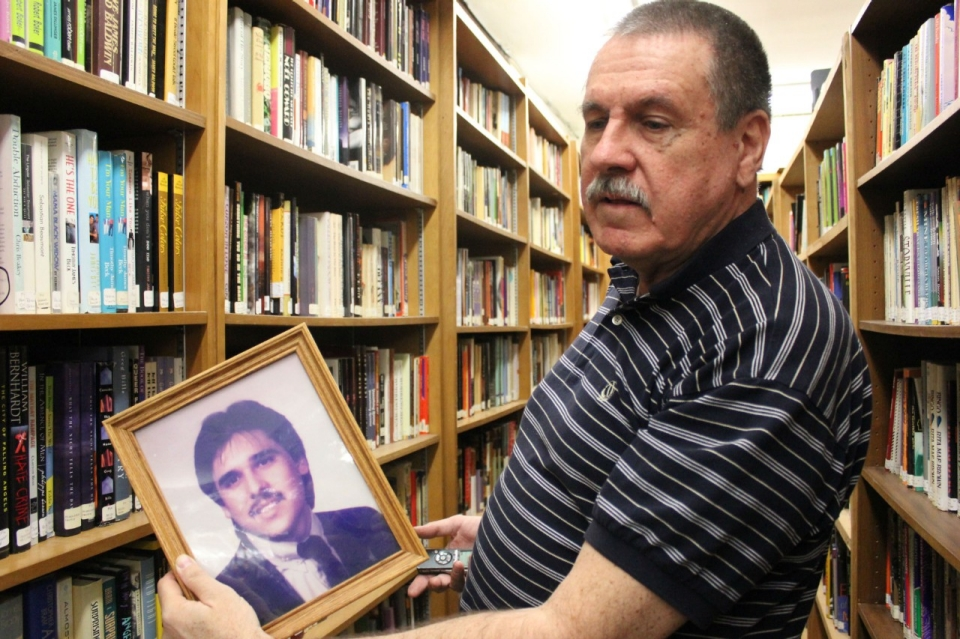 Library founder Michael Bohr with a photo of Chris T. Gonzalez.