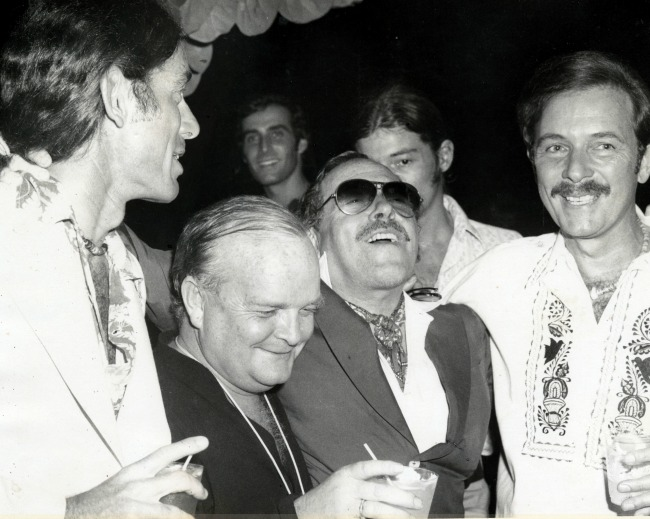 Tennessee Williams (center, with glasses) and Truman Capote (to Williams' right) share a private joke at the Hotel Monteleone.