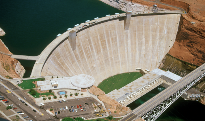 Overview of Glen Canyon Dam. Originally, the bridge was built for truck drivers with materials and equipment for the dam, but now it is for people to drive over in order to get a closer look at the dam. There is the visitor center which is the area with the green grass and parking lot. Visitors can also drive and park on the Dam if they want to get an even closer view. On the bottom right corner of the picture there are spillway tubes where large amounts of water flow out through when released. The powerplant for the hydropower generators is in between the dam and the water.
