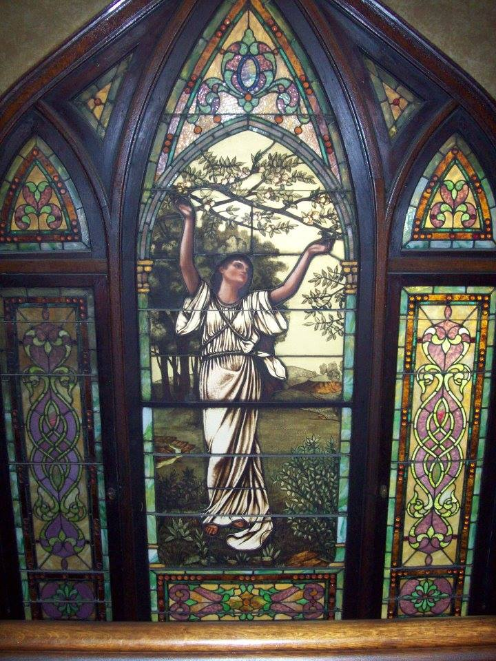 The stained glass on the wall behind the staircase that leads to the second floor.