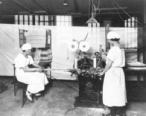 Circa 1915. These women are operating the factory's gum-wrapping machine