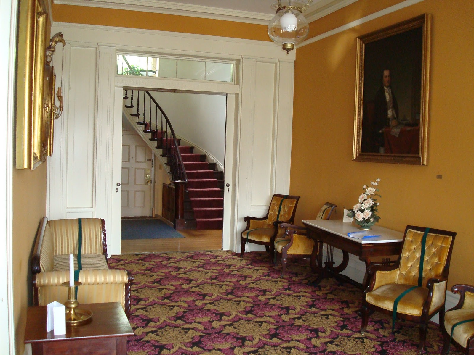The entrance hall to the mansion features period furniture and a family portrait.