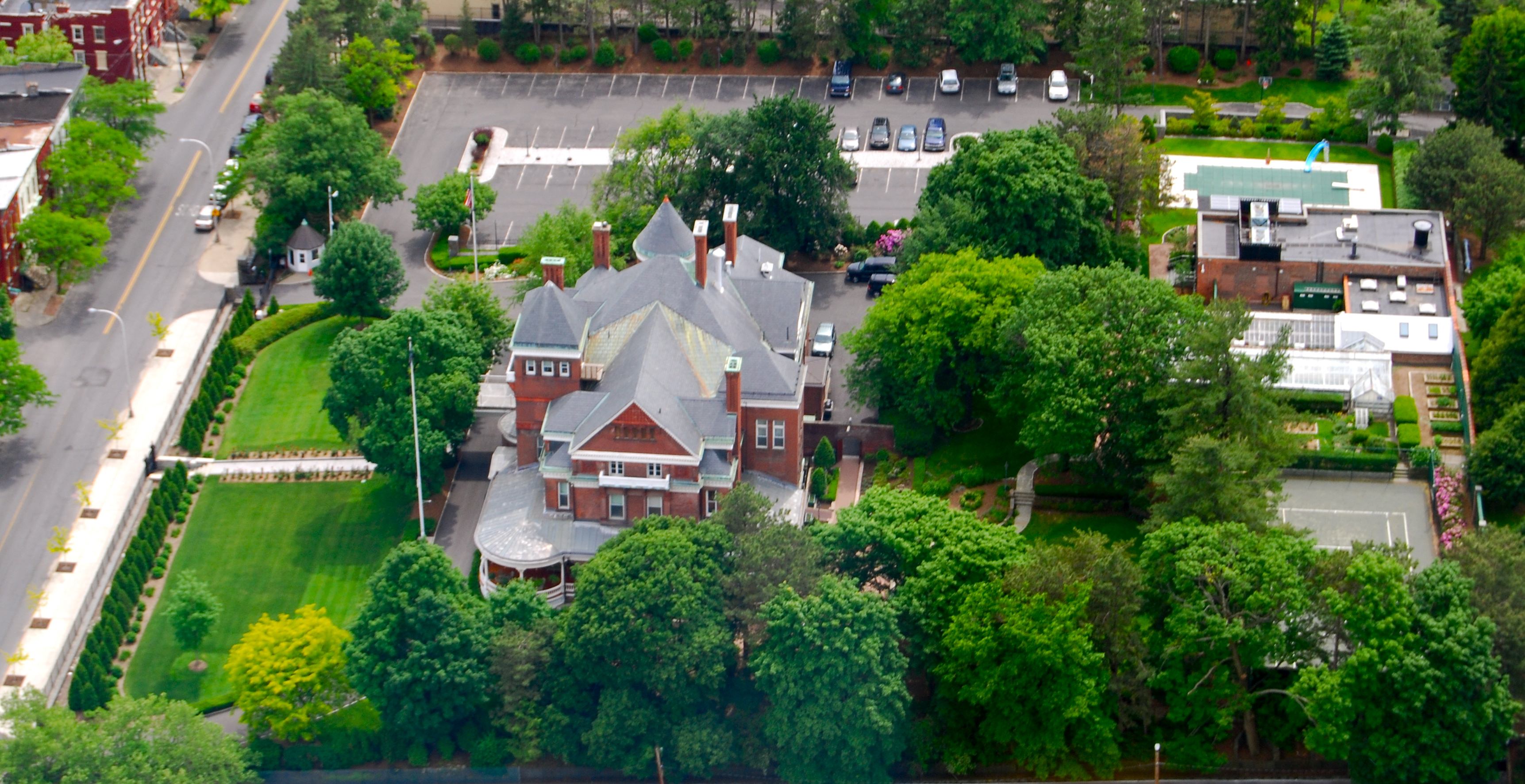 This aerial shot reveals how large the mansion and compound have become, to include an outdoor pool and tennis court.