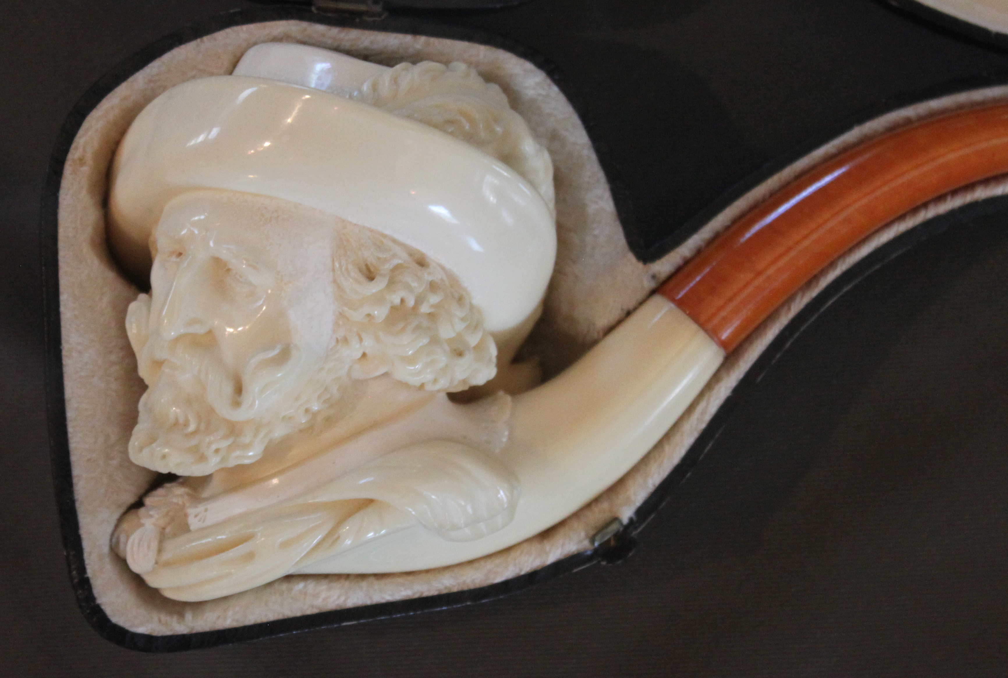 The mineral sepiolite, makes the two meerschaum pipes depicting the likenesses of Peter Paul Ruben and Sire Anthony Van Dyke. Meerschaum can be both carved and polished and the pipes are usually created underwater to maintain the minerals pliability. During the Victorian era, these status symbols were often carved images from history, literature and art but soon gave way to the new look of Art Deco after WWI.