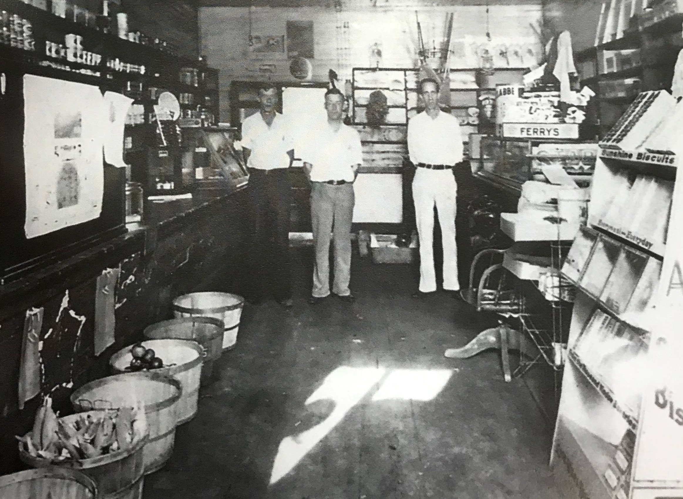 Inside of original Nicely's store. Left to right are Thad Cromptom, clerk and delivery man; A. C. Nicely, owner; and  Eugene Wells, a customer