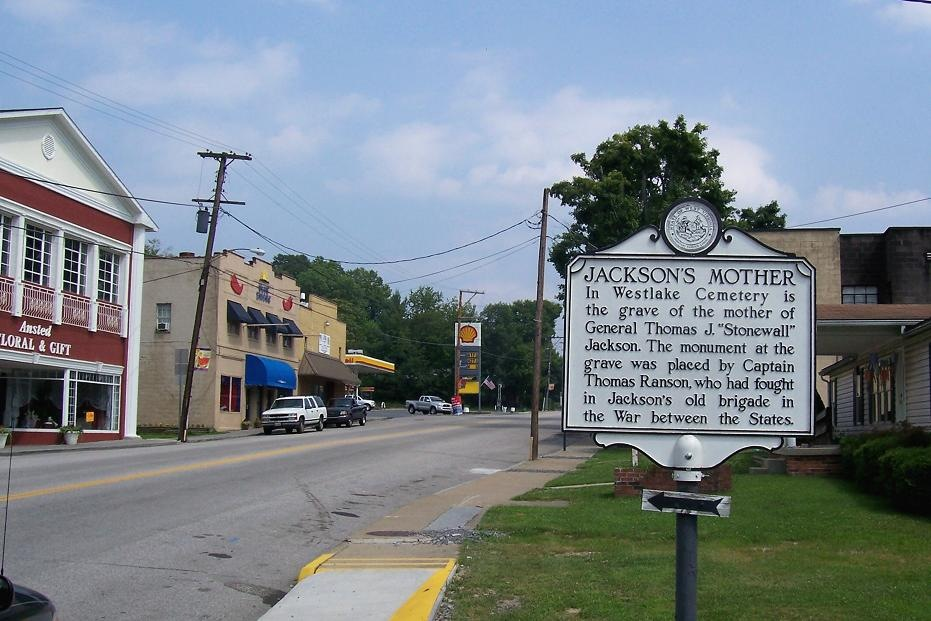 The historical marker is located between a commercial and a residential area in Ansted