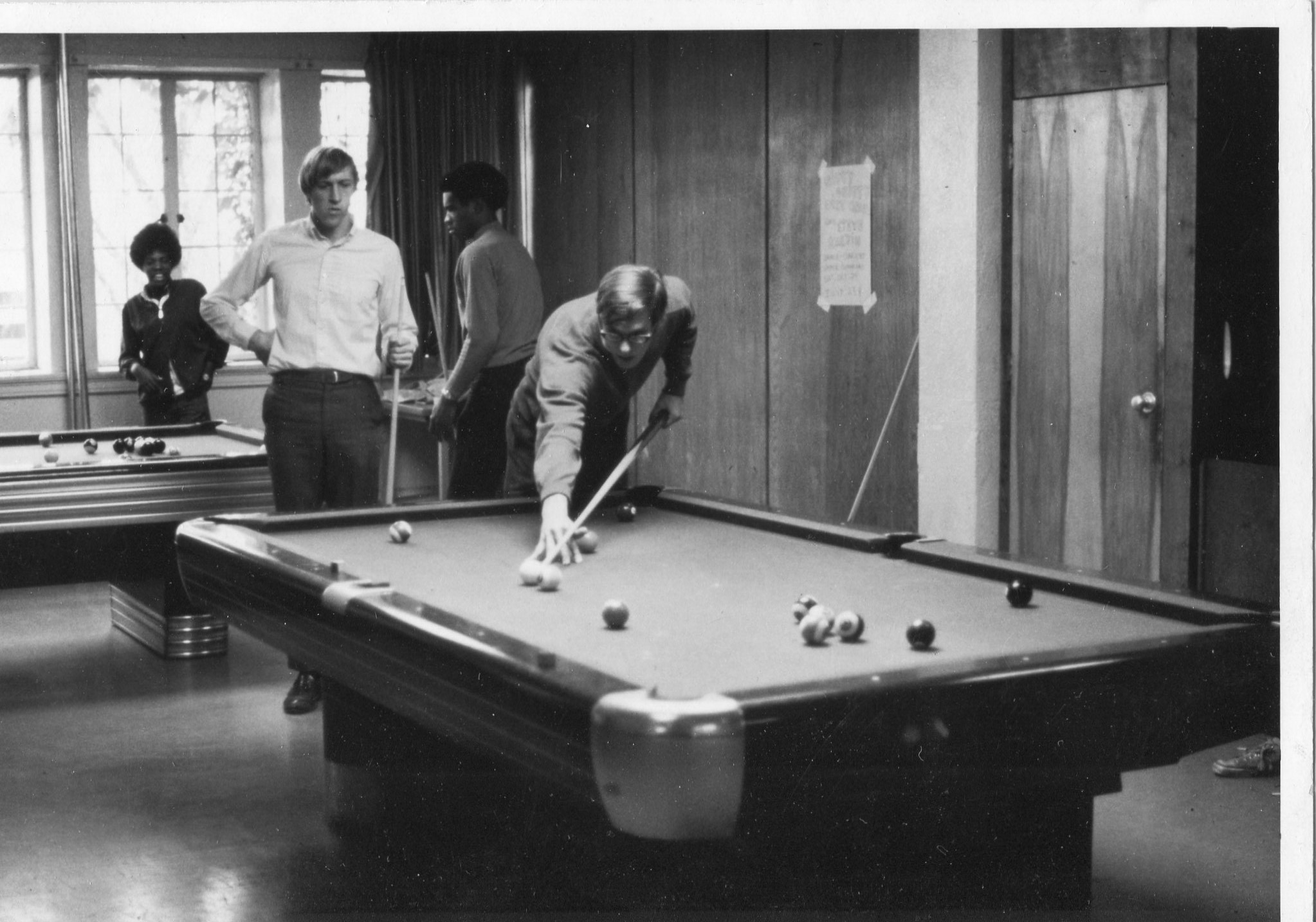 Students playing pool in the common area of Thompson