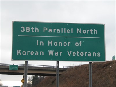38th Parallel Memorial sign with Veterans of All Wars Bridge in the background.
