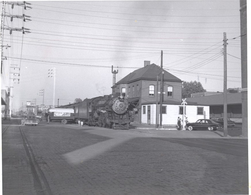 Passenger train pauses in Huntington, 1956. Seems as if a grandfather has come to town for a visit, while a Railway Express Agent unloads packages. Photo by Herbert H. Harwood, Jr., from the Bob Withers Collection. (2013).