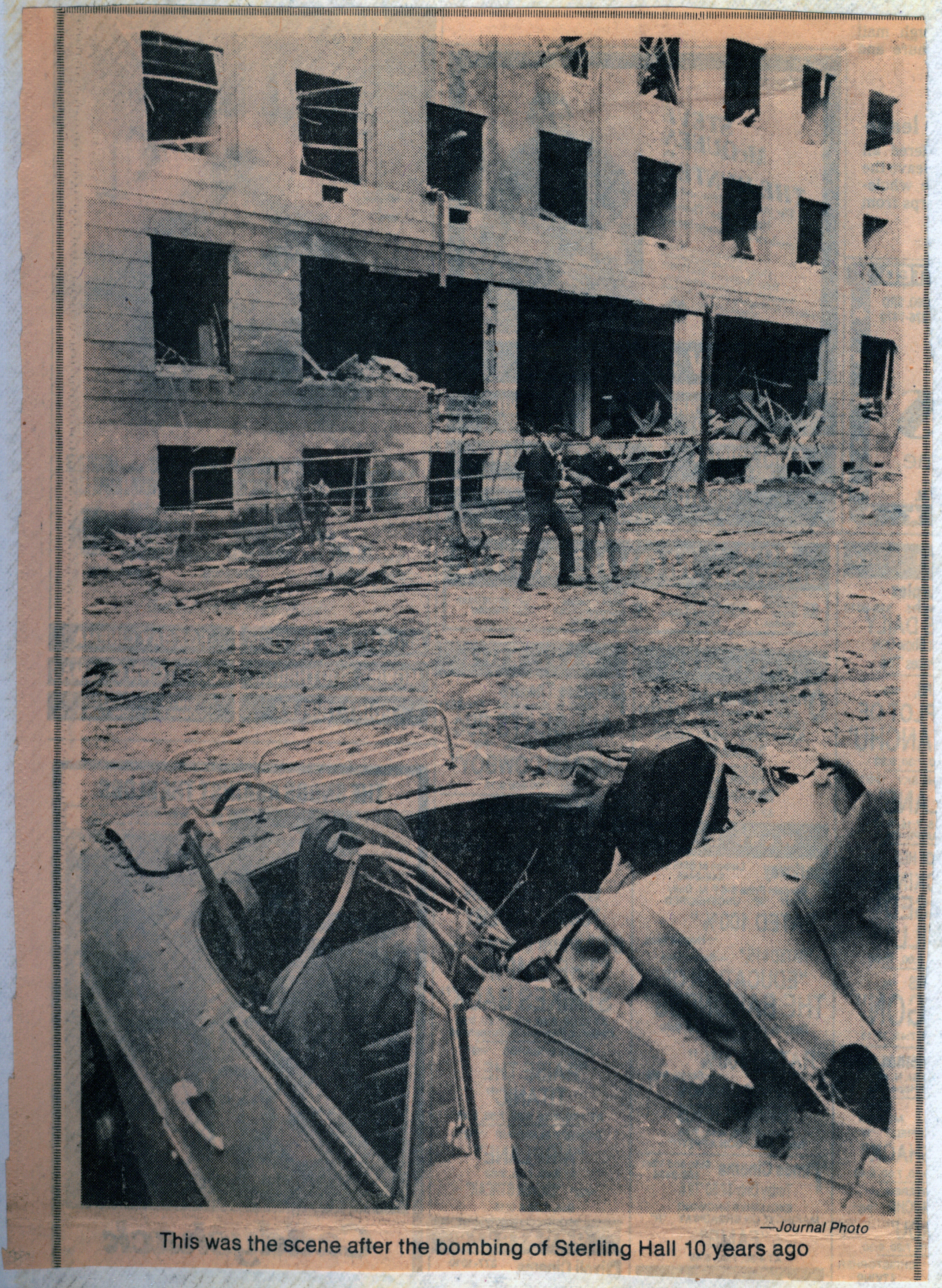 Newspaper clipping printed 10 years after the bombing at Sterling Hall. The image features the wreckage at Sterling Hall, showing two men standing amongst debris, and a car in the front of the image, also filled with debris.