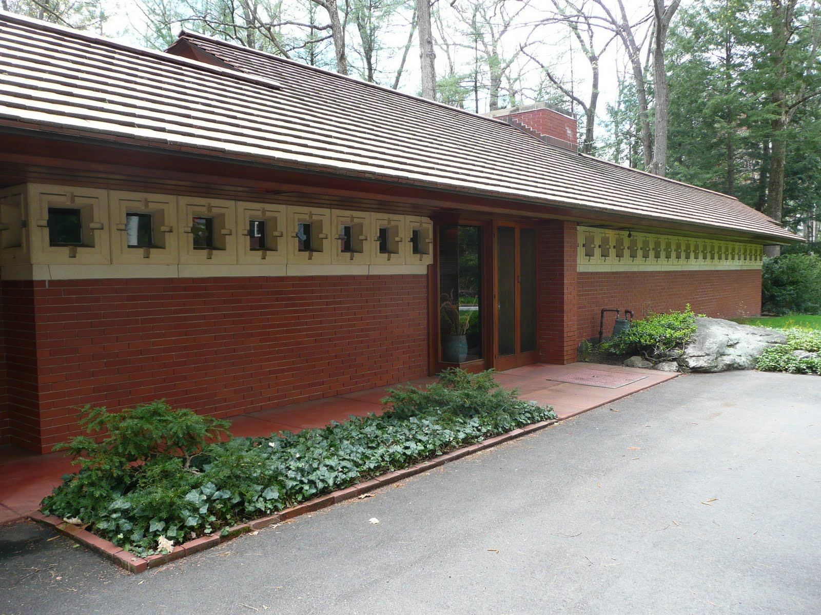 The front or private side of Wright's Zimmerman House with its main entrance and small windows.