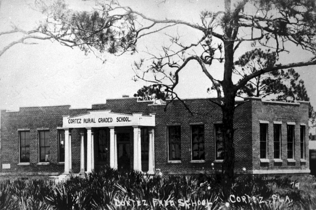 This is an image of the Cortez Rural Graded Schoolhouse, presently the Florida Maritime Museum. Take a minute and notice the pine trees located around the schoolhouse in the 1920s. You can still see pine trees like these ones around the museum's grounds today.